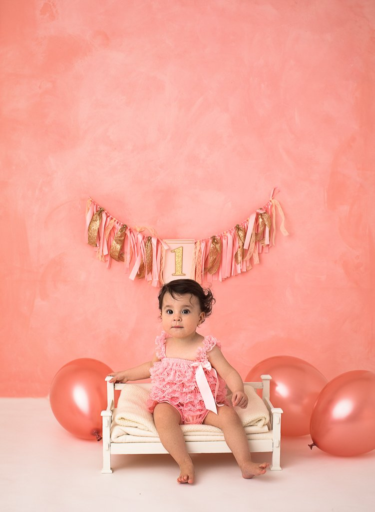 inflating pink balloons is no easy task for a birthday toddler at a cake smash photoshoot