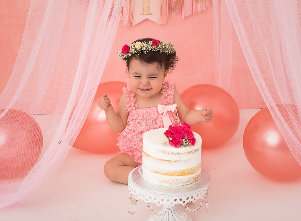 birthday girl smashing cake wearing a floral headband in pink setting